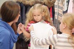 De familie kiest kleren in winkel stock fotografie