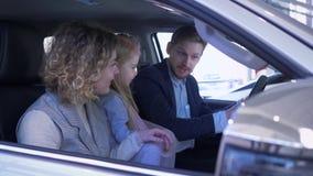 De familie kiest nieuwe auto, gelukkige moeder en vader met kindmeisje die automobiele zitting in cabine overwegen bij autosalon stock video