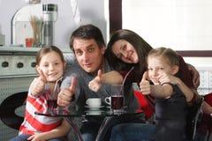 De familie in koffie het tonen beduimelt omhoog Royalty-vrije Stock Foto's