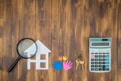 De familie koopt de berekeningen van de huishypotheek, calculator met Magnifie Royalty-vrije Stock Afbeelding