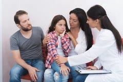De familie kwam een tandarts in een medische kliniek zien Het meisje heeft een tandpijn Stock Foto
