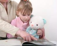 De familie las het boek Stock Foto