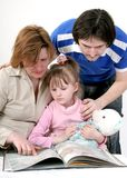 De familie las het boek Stock Afbeelding