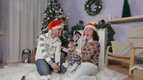 De familie met baby in Kerstman` s hoeden blaast - omhoog een cracker stock videobeelden