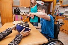 De familie met gehandicapte zoon bakt wafels stock afbeeldingen
