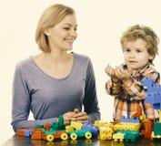 De familie met gelukkige gezichten bouwt stuk speelgoed auto's uit gekleurde bouwblokken Vrouw en jongensspel op witte achtergron Royalty-vrije Stock Foto's