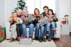 De familie met Kerstmis stelt Zitting op Bank voor Stock Fotografie