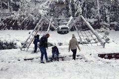 De familie met kinderenspel en heeft pret in sneeuw Royalty-vrije Stock Foto