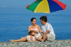 De familie met klein kind zit op een strand Royalty-vrije Stock Afbeeldingen