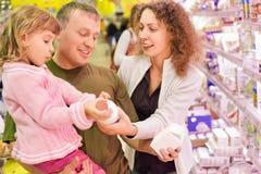 De familie met meisje koopt melk in supermarkt Royalty-vrije Stock Foto's