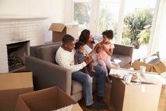 De familie neemt een Onderbreking op Sofa With Pizza On Moving-Dag stock afbeelding