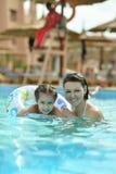 De familie ontspant in pool Stock Fotografie