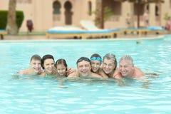 De familie ontspant in pool Stock Afbeeldingen