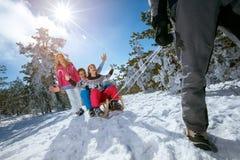 De familie op sneeuw heeft pret het sledding op zonnige de winterdag Stock Afbeeldingen