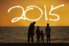 De familie op strand geniet van nieuw jaar 2015 Stock Afbeelding