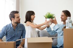 De familie pakt bezittingen uit zittend in woonkamer bij nieuw huis stock foto