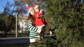 De familie in Santa Claus-kappen verfraait de Kerstboom in openlucht stock footage