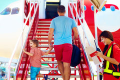 De familie scheept op vliegtuig in, heet de stewardess passagiers welkom Stock Foto