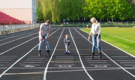 De familie speelt sporten op een renbaan van stadion Stock Afbeeldingen