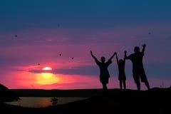 de familie stemt in met de zonsondergangzon Stock Foto