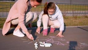 De familie trekt Een kind met moeder schildert met krijt op het asfalt stock footage