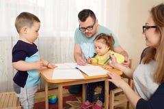 De familie trekt potloden bij een lijst in ruimte stock afbeeldingen