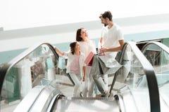 De familie, de vader, de moeder en de dochter gaan op roltrap in winkelcomplex uit royalty-vrije stock fotografie