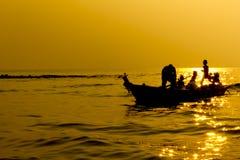De familie van de silhouetvisser op de boot in zonsondergang Stock Afbeeldingen