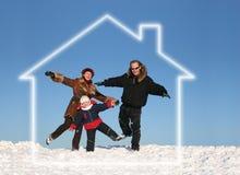 De familie van de winter in droomhuis Stock Afbeeldingen