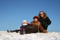 De familie van de winter zit op sneeuw stock afbeeldingen