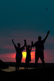 De familie van drie personen stemt in met de zonsondergang Royalty-vrije Stock Foto