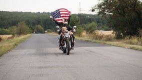 De familie van fietsers met een hond berijdt een motorfiets met een vlag stock videobeelden