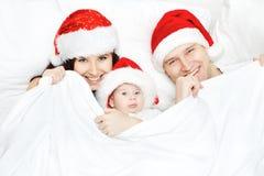 De familie van Kerstmis in rode hoeden die in wit bed liggen Royalty-vrije Stock Afbeeldingen