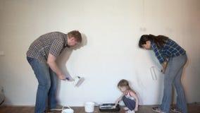 De familie van mamma, papa die, de muur van de dochterverf penseel en rol met behulp van stock videobeelden