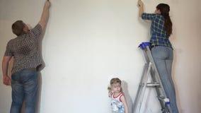 De familie van mamma, papa die, de muur van de dochterverf penseel en rol met behulp van stock video
