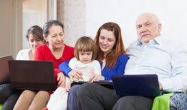 De familie van meerdere generaties samen met weinig apparaten Stock Foto's