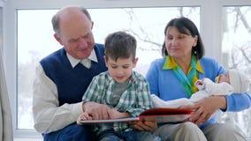 De familie van de opgewektheidgepensioneerde, grootouders met baby leert om jong geitje te lezen stock videobeelden