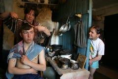 De familie van Russische landbouwers, moeder maakt haar zoon tot een kapsel Stock Afbeeldingen