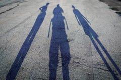 De familie van verlengde schaduwmensen ontwierp op het ruwe asfalt, op een heldere en zonnige dag royalty-vrije stock afbeelding