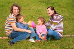 De familie van vier zit op gras