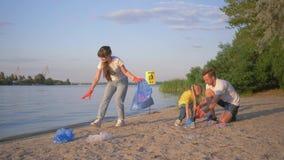 De familie van vrijwilligers, jonge vader en moeder met weinig dochter verzamelt afval in vuilniszak op vuil strand van stock footage