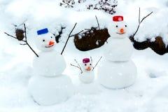 De familie van vrolijke sneeuwmannen verheugt zich bij de aankomst van de winter en de eerste sneeuw stock fotografie