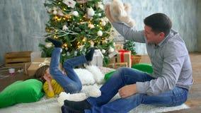 De familie van de winterkerstmis De aantrekkelijke vader en de zeer leuke zoon hebben thuis pret op de achtergrond van Kerstboom stock videobeelden