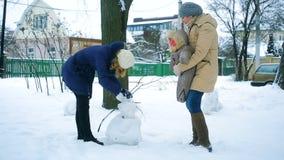 De familie in de winter in het park beeldhouwt een sneeuwman stock videobeelden
