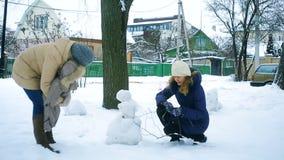 De familie in de winter in het park beeldhouwt een sneeuwman stock footage