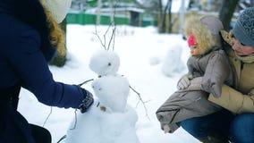 De familie in de winter in het park beeldhouwt een sneeuwman stock video