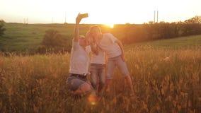 De familie wordt gefotografeerd op een gebied bij zonsondergang De moeder en twee zonen op vakantie maken selfie stock footage