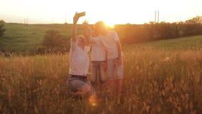 De familie wordt gefotografeerd op een gebied bij zonsondergang De moeder en twee zonen op vakantie maken selfie stock video