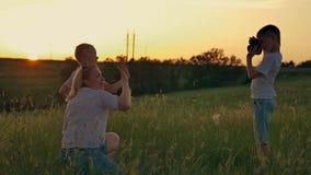 De familie wordt gefotografeerd op een gebied bij zonsondergang De moeder en twee zonen op vakantie maken selfie stock videobeelden