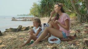 De familie zit op een tropisch strand en eet vruchten in langzame motie stock footage
